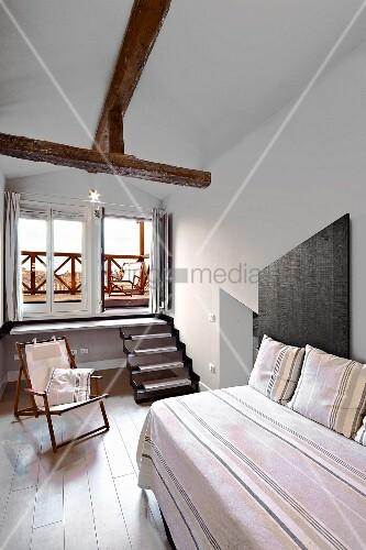 renoviertes zimmer mit einzelbett gestreifte tagesdecke und kissen aus gleichem stoff im. Black Bedroom Furniture Sets. Home Design Ideas
