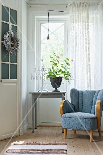 blauer 50er jahre sessel neben einem tisch mit geranie vor dem fenster bild kaufen living4media. Black Bedroom Furniture Sets. Home Design Ideas