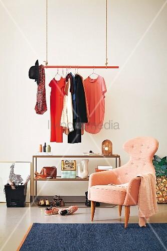 Kleiderstange Hängend abgehängte rote kleiderstange mit damenkleidung und offenes regal in