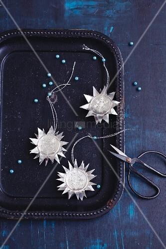 Eisblumen-Sterne aus Teelichtern als Aufhänger für den Weihnachtsbaum