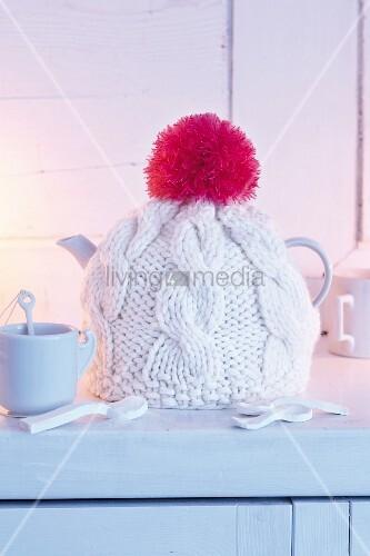 Selbstgestrickte Teekannen-Mütze mit Bommel