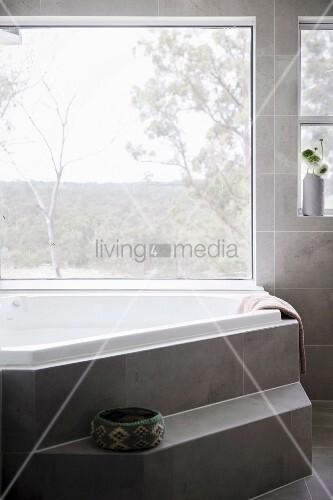 polygonale badewanne mit stufe vor panoramafenster an wand und auf boden grau marmorierte. Black Bedroom Furniture Sets. Home Design Ideas