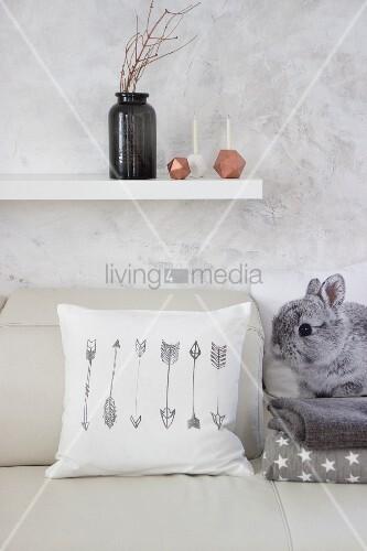 Weiss bezogenes Kissen mit aufgedruckten Pfeilmotiven