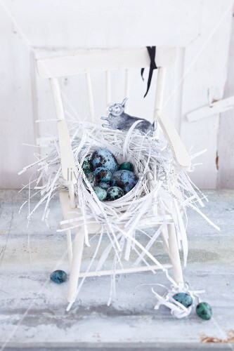 Osternest aus Papierstreifen gefüllt mit blauen und grünen Eiern