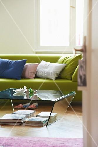 blick auf hellgr nes sofa mit kissen und plexiglastisch. Black Bedroom Furniture Sets. Home Design Ideas