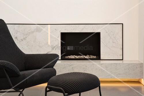 edle moderene marmorkaminverkleidung mit indirekter beleuchtung und designersessel bild kaufen. Black Bedroom Furniture Sets. Home Design Ideas