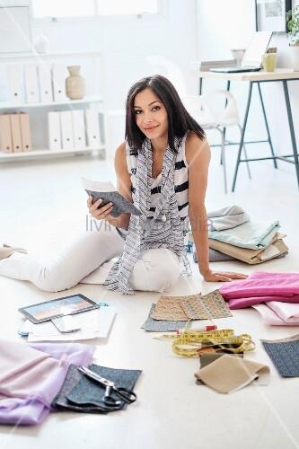 Modedesignerin zwischen stoffmustern und n hutensilien auf for Boden mode preview
