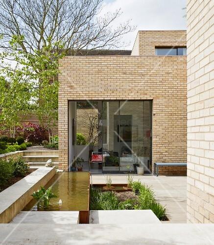 geometrische terrassengestaltung mit pflanzbeet und wasserbecken eines modernen. Black Bedroom Furniture Sets. Home Design Ideas