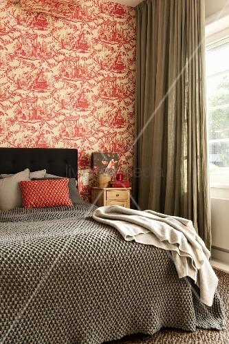 tagesdecke auf doppelbett mit kopfteil vor tapezierter wand mit rot weissem toile de jouy muster. Black Bedroom Furniture Sets. Home Design Ideas