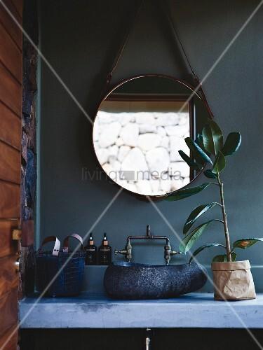 beton waschtisch mit waschsch ssel aus stein dar ber runder spiegel an petrolfarbener wand. Black Bedroom Furniture Sets. Home Design Ideas