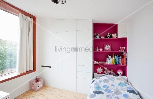kinderzimmer mit bett vor pinkfarbenem regal und weissem einbauschrank bild kaufen living4media. Black Bedroom Furniture Sets. Home Design Ideas