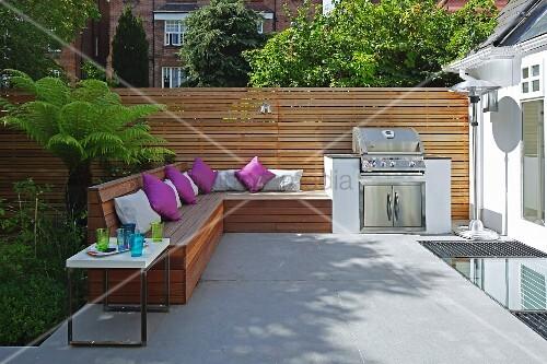 eingebaute holzbank mit violetten kissen und grill auf sommerlicher terrasse moderner. Black Bedroom Furniture Sets. Home Design Ideas