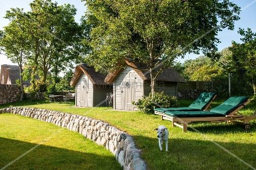 terrassierter garten mit naturstein b schung hund vor sonnenliegen mit gr nen auflagen bild. Black Bedroom Furniture Sets. Home Design Ideas