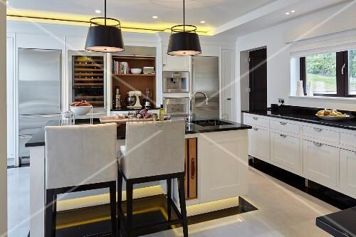 Große Küche in Schwarz-Weiß mit Kochinsel, Spots an Boden und ...