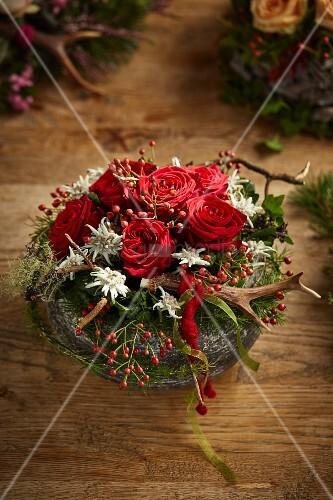 gesteck im alpinen stil mit roten rosen geweih und edelweiss bild kaufen living4media. Black Bedroom Furniture Sets. Home Design Ideas