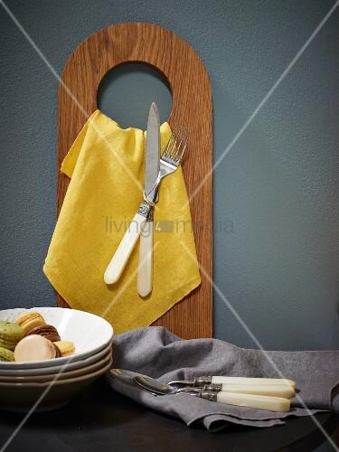 gelbe serviette und besteck h ngen an holzbrett mit loch bild kaufen living4media. Black Bedroom Furniture Sets. Home Design Ideas