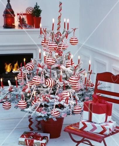 rot wei geschm ckter christbaum mit geringelten weihnachtskugeln und roten brennenden. Black Bedroom Furniture Sets. Home Design Ideas