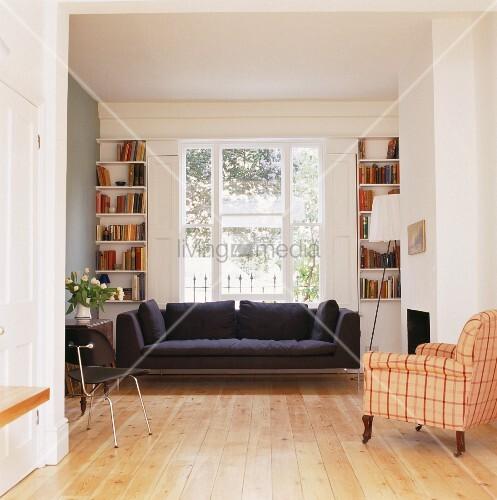 schwarzes sofa unter fenster und antiker sessel mit kariertem bezug im offenen wohnzimmer bild. Black Bedroom Furniture Sets. Home Design Ideas