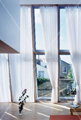 atelierfenster mit weissem vorhang und blumenvase auf. Black Bedroom Furniture Sets. Home Design Ideas