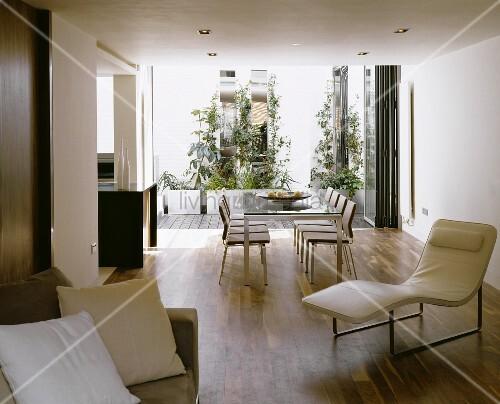 offener wohnraum mit weisser lederliege vor esstisch mit st hlen und terrassenblick bild. Black Bedroom Furniture Sets. Home Design Ideas