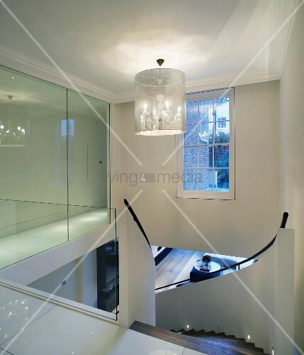designer treppenhaus mit h ngelampe und glastrennwand neben geschwungener treppe bild kaufen. Black Bedroom Furniture Sets. Home Design Ideas