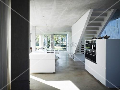 offener wohnraum mit decke und boden aus beton und weissem freistehendem k chenblock vor treppe. Black Bedroom Furniture Sets. Home Design Ideas