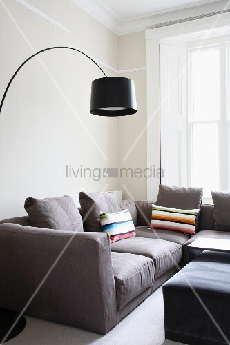 moderne wohnraumecke bogenlampe mit schwarzem schirm ber hellgrauem sofa bild kaufen. Black Bedroom Furniture Sets. Home Design Ideas