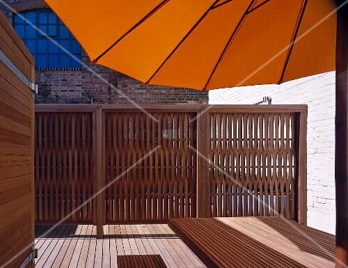 aufgespannter gelber sonnenschirm auf holzterrasse und. Black Bedroom Furniture Sets. Home Design Ideas