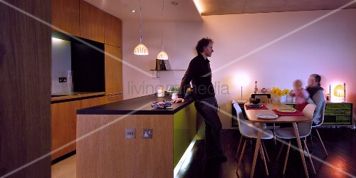 familie am esstisch vor hinterleuchteter k chentheke im offenen wohnraum bild kaufen. Black Bedroom Furniture Sets. Home Design Ideas