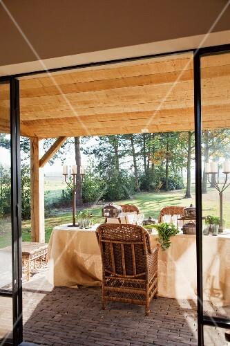 blick durch offene terrassent r auf gedeckten tisch vor l ndlichem garten bild kaufen. Black Bedroom Furniture Sets. Home Design Ideas