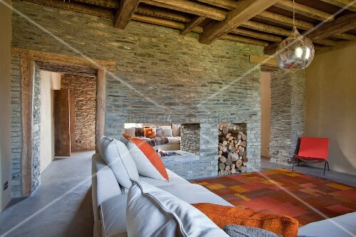 moderner wohnraum mit rustikaler holzbalkendecke und kaminwand aus,