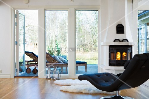 schwarze designer liege vor dem kamin und der terrasse bild kaufen living4media. Black Bedroom Furniture Sets. Home Design Ideas