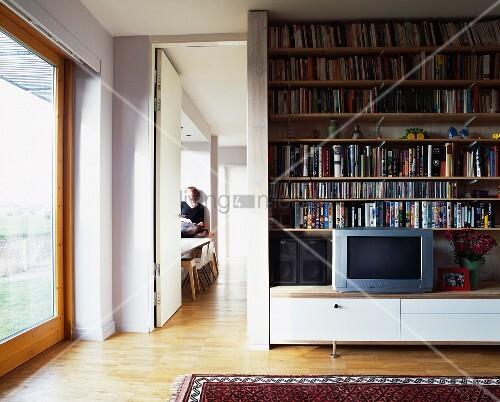 b cherregal und fernseher auf bodennahem sideboard neben. Black Bedroom Furniture Sets. Home Design Ideas