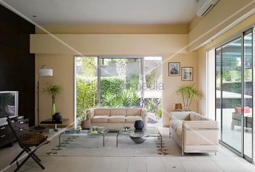 Wohnzimmer Mit Cremefarbenen Sofas Im Bauhausstil Vor Grossen Schiebefenstern