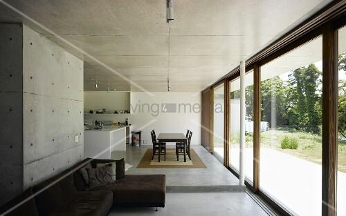 sichtbeton im offenen wohnraum mit k che und essplatz vor breiter terrassen fensterfront mit. Black Bedroom Furniture Sets. Home Design Ideas