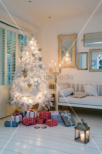 weihnachtsstimmung weisser tannenbaum und geschenke in zimmerecke eines l ndlichen wohnraumes. Black Bedroom Furniture Sets. Home Design Ideas