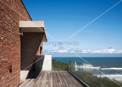 blick von der terrasse mit glasgel nder auf das meer. Black Bedroom Furniture Sets. Home Design Ideas