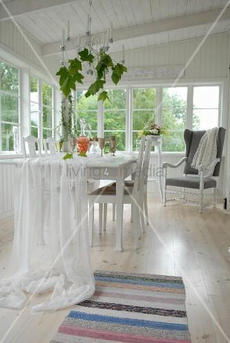 weisser stoff auf esstisch drapiert in der loggia eines weissen holzhauses bild kaufen. Black Bedroom Furniture Sets. Home Design Ideas