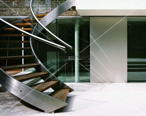 Geschwungene Treppe aus Edelstahl und Holzstufen im Innenhof eines ...