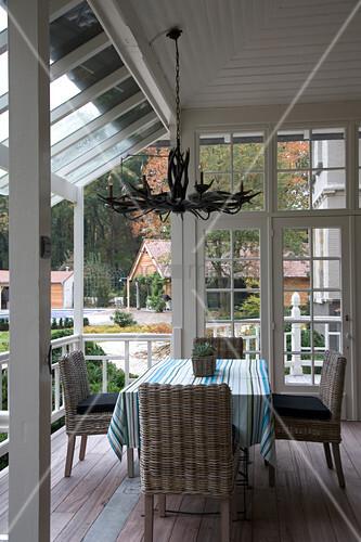 rattanst hle um tisch mit gestreifter tischdecke auf terrasse eines landhauses bild kaufen. Black Bedroom Furniture Sets. Home Design Ideas