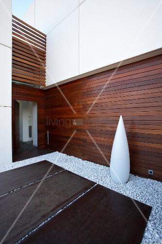 hell und dunkel verschalte moderne hausfassade davor stahlplatten auf einem bett aus weissen. Black Bedroom Furniture Sets. Home Design Ideas