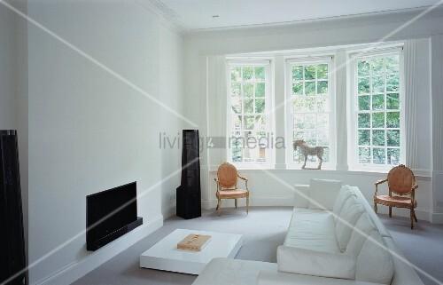 Moderne Wohnzimmergestaltung mit weissem Sofa vor Kamin im ...