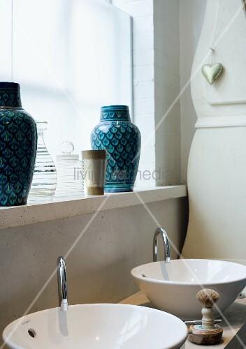 zwei waschtische zwei vasen auf ablage vor fenster bild kaufen living4media. Black Bedroom Furniture Sets. Home Design Ideas
