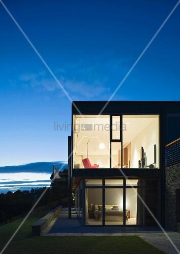 haus mit glasfront in abendbeleuchtung bild kaufen. Black Bedroom Furniture Sets. Home Design Ideas