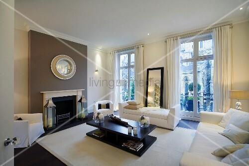 Moderne, weisse Polstermöbel und schwarzer Wohnzimmertisch in ...