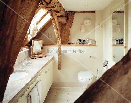 niedriges cremefarbenes bad mit marmorwaschtisch unter sichtbaren alten dachbalken und. Black Bedroom Furniture Sets. Home Design Ideas