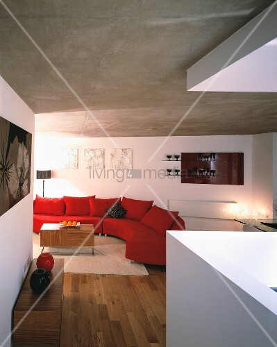 betondecke wohnraum mit roter geschwungener couch unter grauer verputzen oder streichen