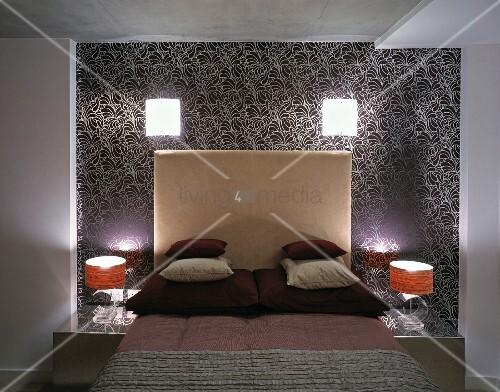 kissenstapel auf bett mit hohem kopfteil und leuchten an wand mit gemusterter tapete bild. Black Bedroom Furniture Sets. Home Design Ideas