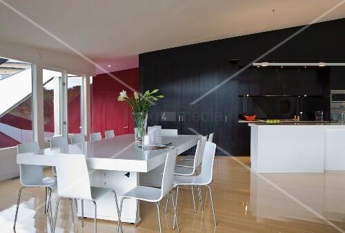 moderner esstisch und st hle in weiss vor freistehender k chentheke und schwarzem einbauschrank. Black Bedroom Furniture Sets. Home Design Ideas