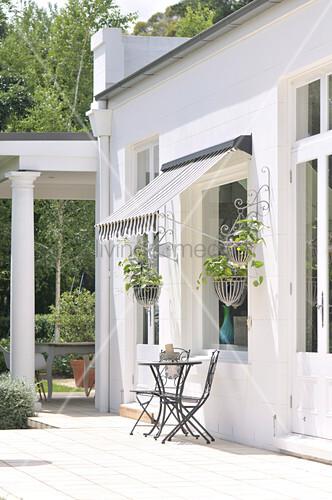 terrassenpl tzchen mit markise vor weiss get nchtem haus und berdachte terrasse im kolonialstil. Black Bedroom Furniture Sets. Home Design Ideas